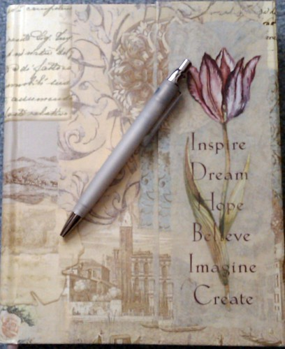 journal with inspiring word on it and a pen
