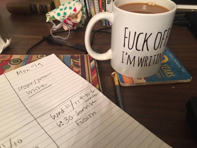 cup on desk with writing plan